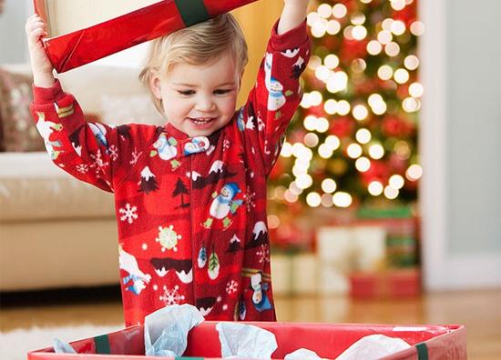 Imagem mostrando uma criança abrindo um presente no natal